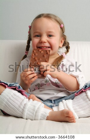 Four years old with a large block of chocolate with hazelnuts. - stock photo