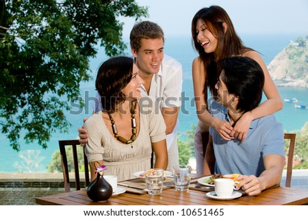 Four young adults at breakfast with ocean view behind - stock photo