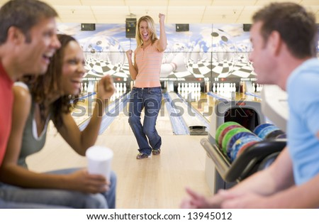 Four young adults cheering in a bowling alley - stock photo
