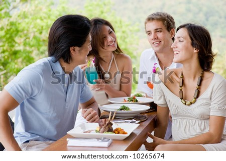 Four young adults enjoying a meal together on vacation - stock photo