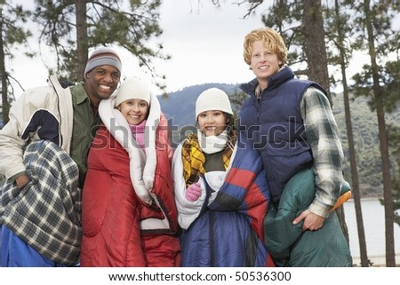 Four young adults wrapped in sleeping bags, standing by lake - stock photo