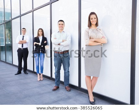 Four young and successful business people standing in front of the modern office building. Focus on confident young businesswoman standing with her arms crossed in front of her business team. - stock photo