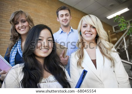 Four young, attractive students at school together - stock photo
