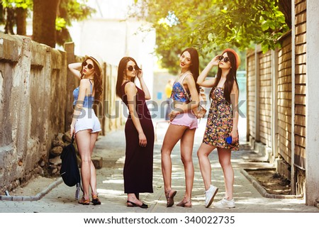 four young beautiful girls posing in the alley
