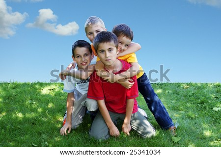 Four young boys hugging on the grass