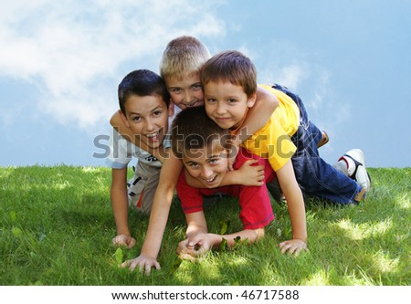 Four young boys lying and hugging on the grass - stock photo