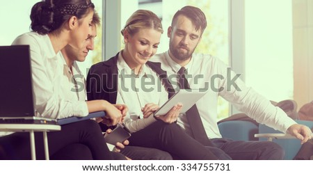 Four young business people sitting in a conference room, preparing for a meeting