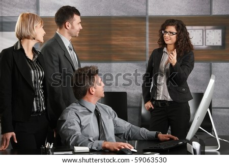 Four young business people talking in office.? - stock photo