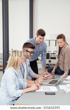 Four Young Businesspeople Looking at the Laptop Screen Together While Having a Meeting Inside the Boardroom.