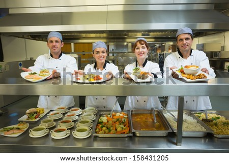 Four young chefs showing plates standing in a modern kitchen - stock photo
