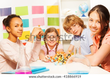 Four young chemists studying molecular structure - stock photo