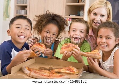 Four young children indoors with woman eating pizza smiling - stock photo