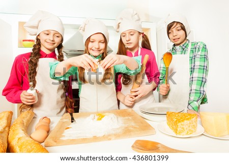 Four young cooks learning to prepare bakery dough - stock photo