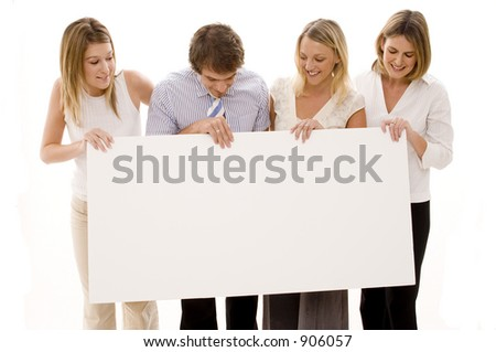 Four young executives holding a big blank sign - stock photo