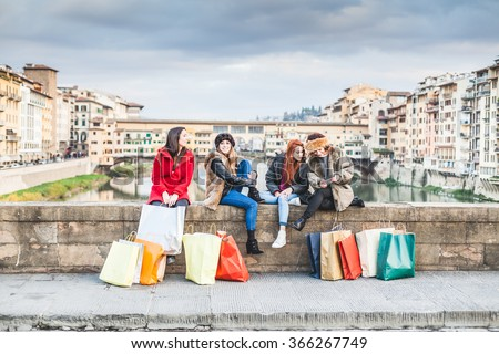 Four young female friends take a break from shopping for the city shops. Are sitting on the railing of a bridge, two talk while two look phone, shopping bags around them, behind them the Ponte Vecchio - stock photo