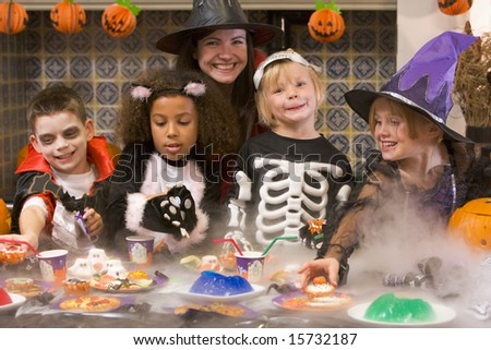 Four young friends and a woman at Halloween eating treats and smiling - stock photo