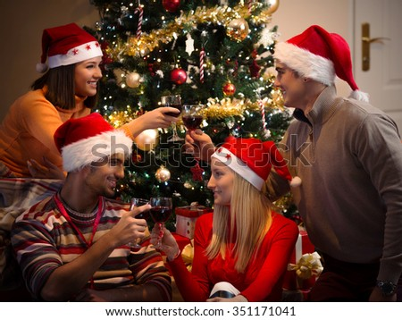 Four young friends celebrating New Year and toasting with wine - stock photo