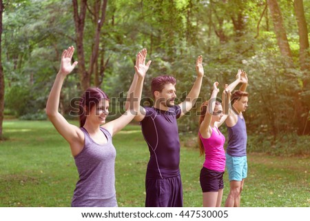 Four young friends doing aerobics exercises outdoors in a park standing in a line with their arms raised in a healthy active lifestyle concept - stock photo