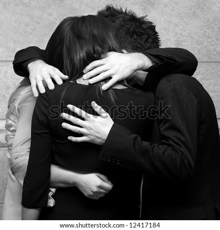 Four young friends holding each other in a private moment - stock photo