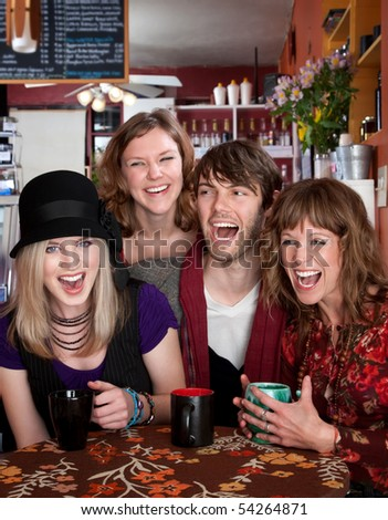 Four young friends laughing in a cafe - stock photo