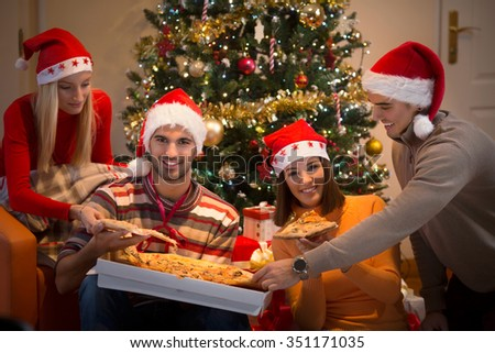 Four young friends sharing pizza and wearing Santa hats while sitting in front of the Christmas tree
