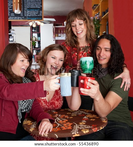 Four young friends toasting at a cafe - stock photo