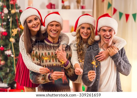 Four young friends, two girls and two boys while celebrating Christmas at home - stock photo