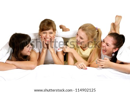 Four young girl lying on the bed - stock photo