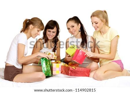 Four young girl with gifts on bed - stock photo