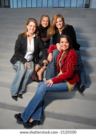 four young girls in business attire on steps - stock photo