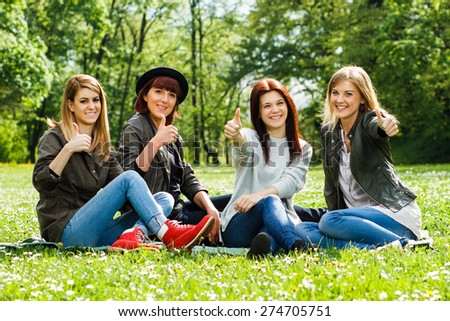 Four young girls sitting in the park and showing thumbs up.Girls showing thumbs up - stock photo