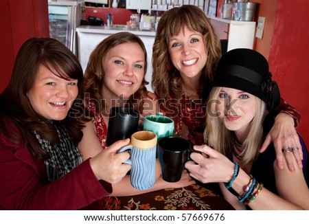 Four young happy female friends at a cafe - stock photo