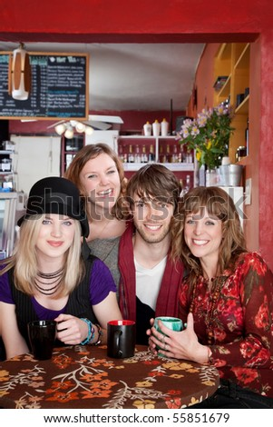 Four young happy friends at a cafe - stock photo