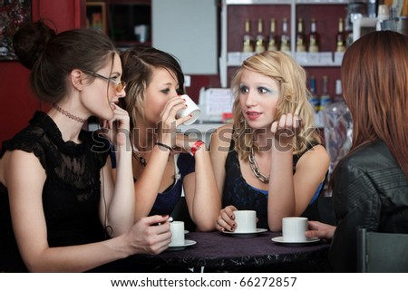 Four young ladies with coffee in a cafe
