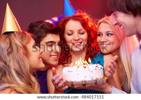 Four young people congratulating their friend, presenting her a birthday cake, looking at her and the cake and smiling