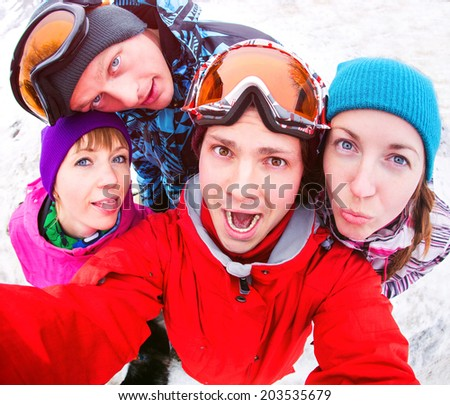Four young people fun portrait in winter clothes - stock photo