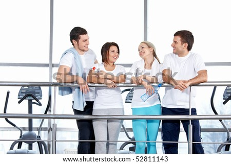 Four young people in sports suits in fitness club - stock photo