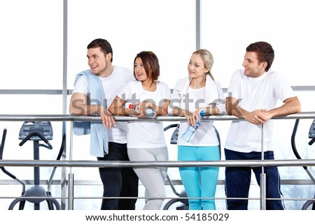 Four young people in sportswear look aside - stock photo