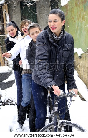 four young people relaxing on bicycle in snow - stock photo