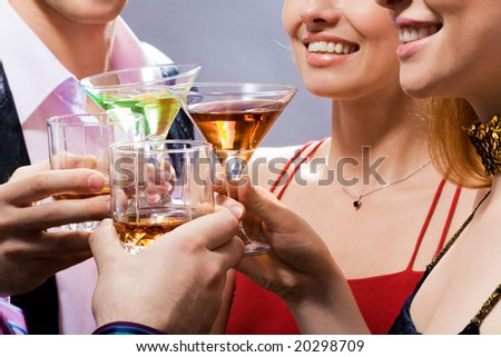 Four young people touch glasses in a toast - stock photo