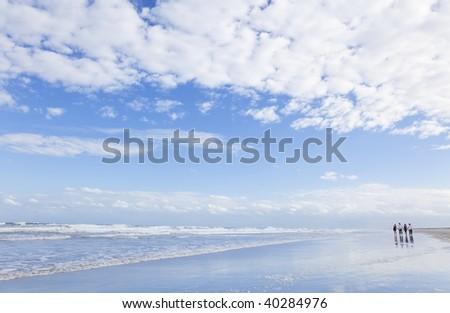 Four young people, two couples, holding hands, walking down on a deserted beach