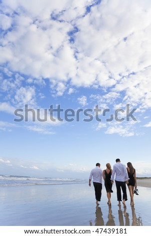 Four young people, two couples, holding hands, walking together on a deserted  beach with a blue sky and clouds.