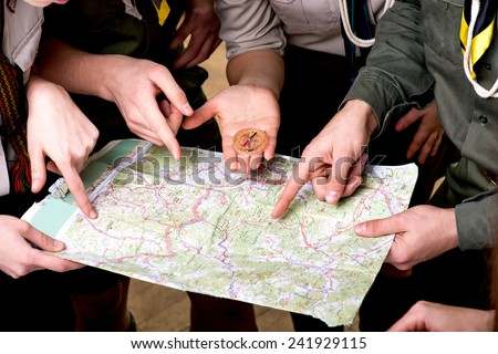 Four young scout members in uniform looking to the map and compass. Close plan without face - stock photo