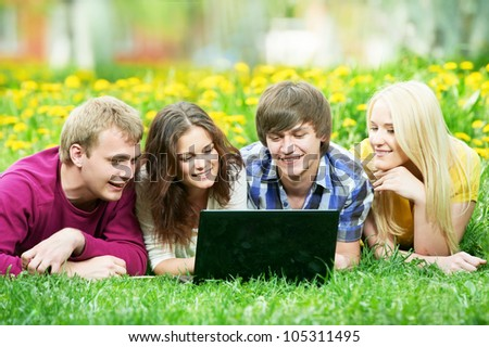 Four young students group with computer studying in spring outdoors - stock photo