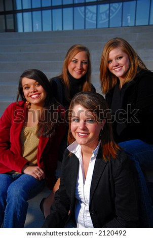 Four young students in professional dress, focus on front center girl. - stock photo
