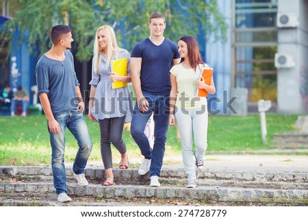 Four young students talking in university campus - stock photo