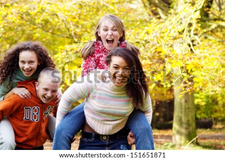Four young teenager friends playing piggy bag racing game in a park forest during the fall autumn season with yellow trees, having fun, laughing and screaming together. - stock photo