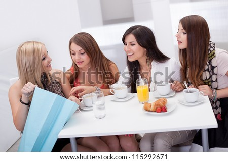 Four young women friends seated at a coffee table looking at shopping purchases in a carrier bag held by one of them - stock photo