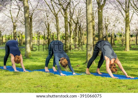 Four young women practicing Lotus Pose for opening up the hips and creating flexibility in the ankles and knees - stock photo