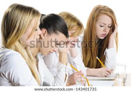 Four young women sitting at a table and write a focused examination, isolated against white background. - stock photo